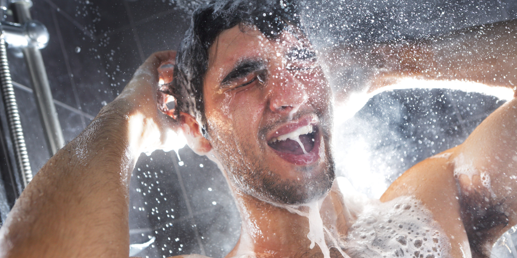 Man in shower, rinsing shampoo from hair